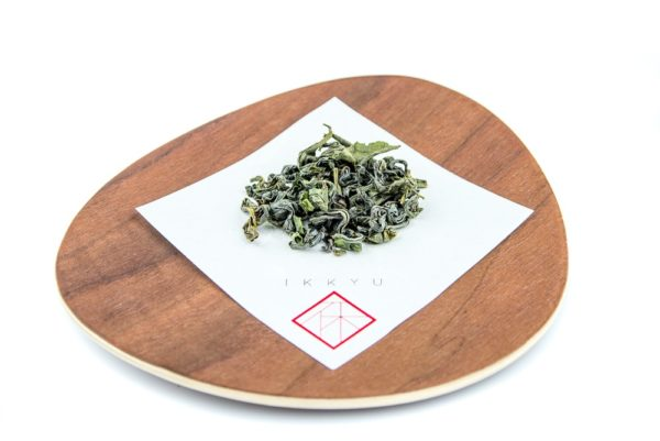 leaves of organic kamairicha on a wooden plate