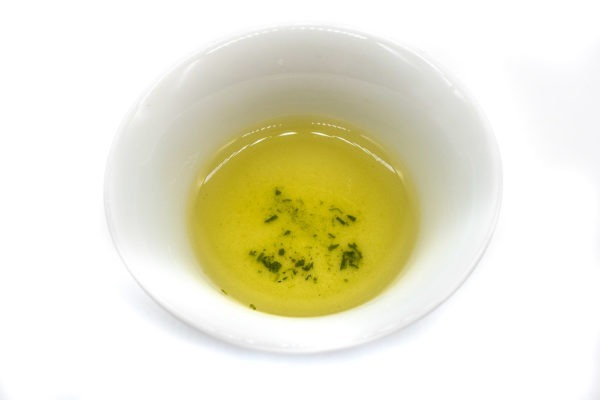 Top view of a small white porcelain cup against a white background filled with golden-green brewed dento hon gyokuro green tea from Yame.