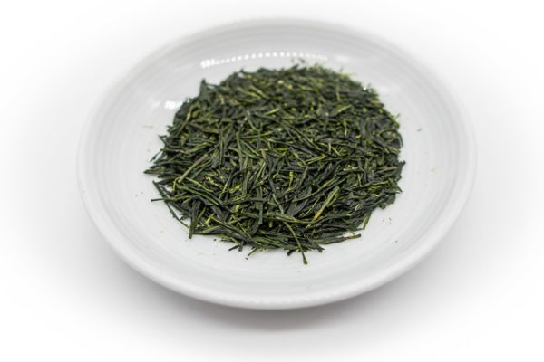 Needle-shaped and deep emerald green dento hon gyokuro leaves from Yame, Japan, in a circle shape, on a small round white dish..