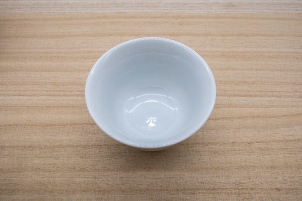 Small Japanese tea cup in white porcelain made in Arita, Japan, made for drinking gyokuro green tea, placed on a wooden plank.