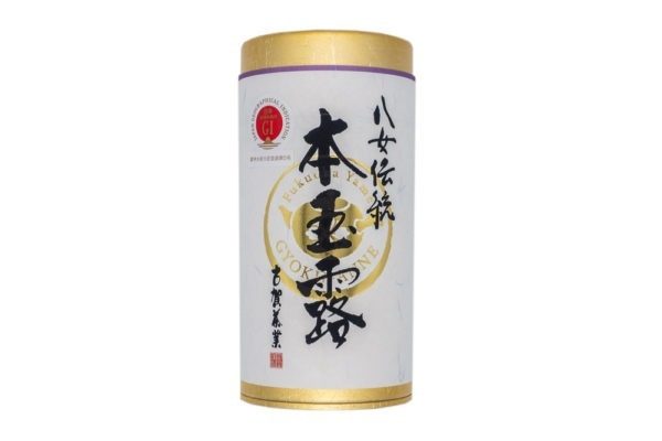 Tube-shaped golden box with a white paper label wrapped around it with hand-written Japanese calligraphy on it, with the words 'dento hon gyokuro, Yame tea'.