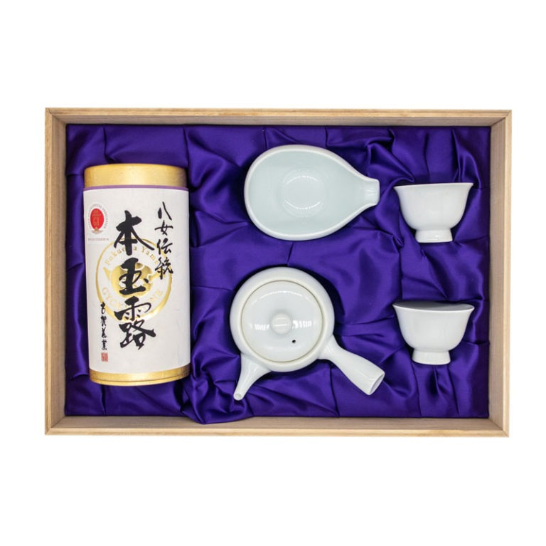 Open wooden box containing a set made of a tube-shaped golden box with a white paper label wrapped around it with hand-written Japanese calligraphy, a white porcelain tea pot, a white porcelain water cooler and two small white porcelain tea cups resting against a deep purple velvet tissue.