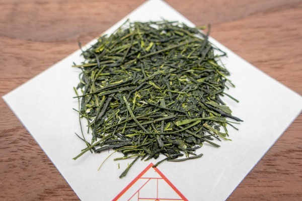Needle-shaped and deep emerald premium sencha green tea leaves from Yame, Japan on a square white sheet of paper on a wooden plate.