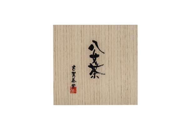 Top view of a large square wooden box with Japanese hand calligraphy written on it in black ink.