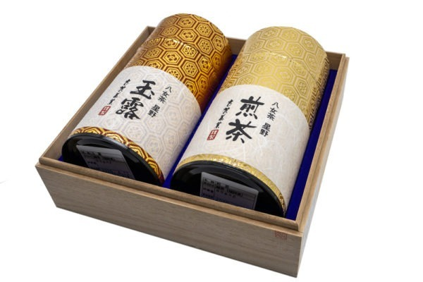 Side view of two shiny golden tube-shaped green tea boxes laying inside a wooden box with Japanese hand-written calligraphy on their labels marking their contents (Yame gyokuro and Yame sencha).