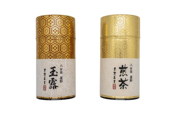 Front view of two shiny golden tube-shaped green tea boxes with Japanese hand-written calligraphy on their labels marking their contents (Yame gyokuro and Yame sencha).