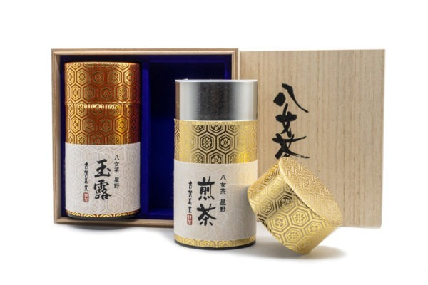 Front view of two shiny golden tube-shaped green tea boxes in front of a wooden box with Japanese hand-written calligraphy on their labels marking their contents (Yame gyokuro and Yame sencha). One of the tubes is open, the lid resting next to it.