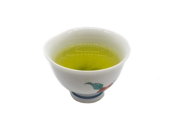 Side view of a small white porcelain cup filled with brewed premium Japanese sencha green tea.
