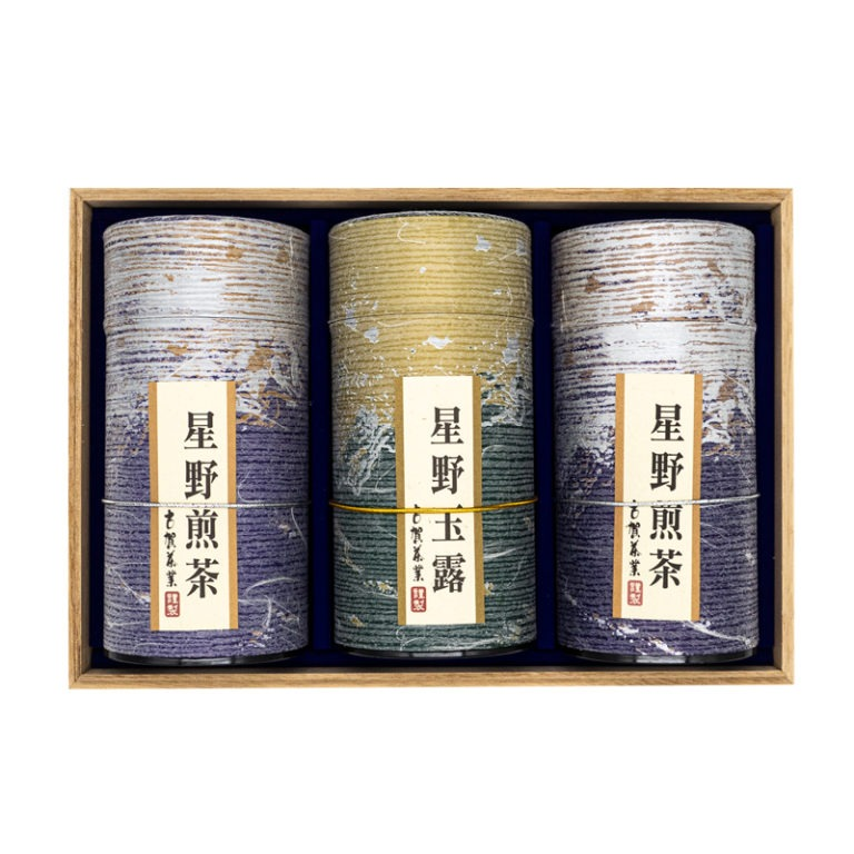 Front view of three purple and golden tube-shaped green tea boxes placed inside a wooden box with Japanese markings on them mentioning their origins (Hoshino sencha and gyokuro).