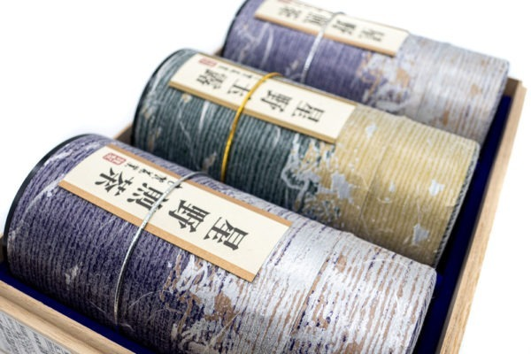 Close view of three purple and golden tube-shaped green tea boxes with Japanese markings on them mentioning their origins (Hoshino sencha and gyokuro).