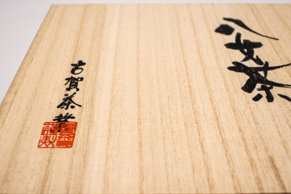 Large square wooden box with Japanese hand calligraphy written on it in black ink.