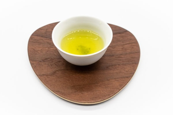 Side view of a small white porcelain cup filled with brewed premium Japanese sencha green tea on a triangular-shaped wooden plate.