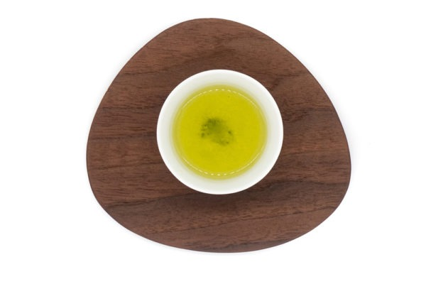 Top view of a small white porcelain cup filled with brewed premium Japanese sencha green tea on a triangular-shaped wooden plate.
