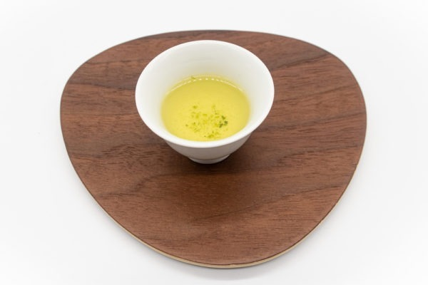 Side view of a small white porcelain cup filled with brewed dento hon gyokuro green tea on a triangular-shaped wooden plate.