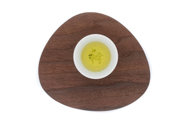 Top view of a small white porcelain cup filled with brewed dento hon gyokuro green tea on a triangular-shaped wooden plate.