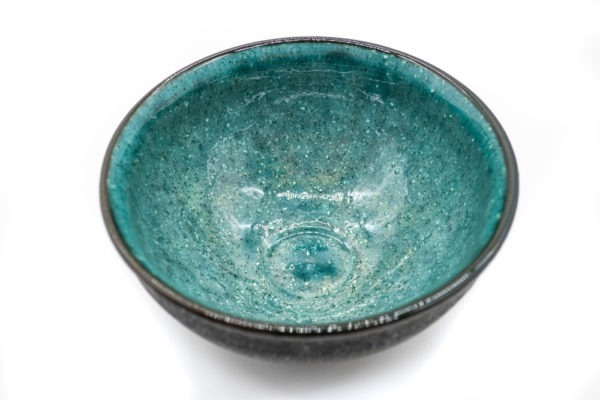 Inside of a matcha bowl, with a dark grey and rough outside and a vibrant and glazed turquoise color on the inside.