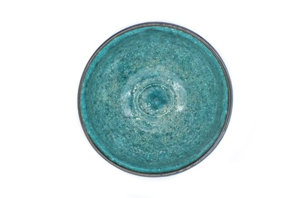 Inside of a matcha bowl, showing its vibrant and glazed turquoise color.
