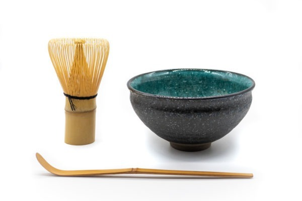 Front side of a matcha bowl, with a dark grey and rough outside and a vibrant and glazed turquoise color on the inside, next to a matcha whisk and a matcha spoon.