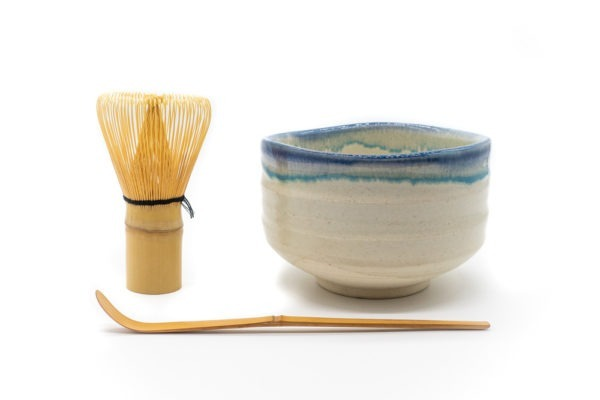 Front of a cream-white matcha bowl with a blue-colored glaze all around its uneven edge, with matcha whisk and a matcha spoon next to it.