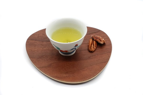 White porcelain cup filled with pale green brewed premium Japanese white tea on a triangular-shaped wooden plate, with two roasted nuts next to it.
