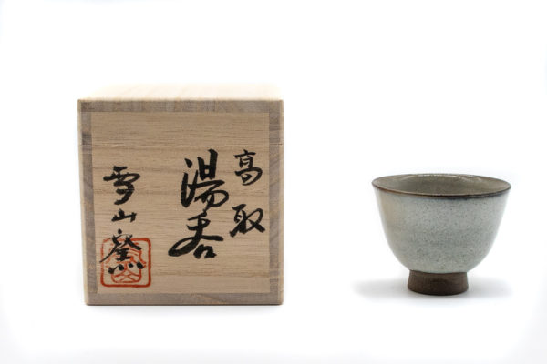 Front side of a small and delicate grey handmade cup for drinking gyokuro green tea, made in Koishiwara, Fukuoka, Japan by Onimaru the Second, next to a wooden box with hand Japanese calligraphy that accompanies the cup.